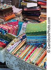 Fabric store with stacks of colorful textiles - Traditional...