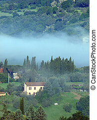 Fabulous landscape of the foggy morning in Tuscany
