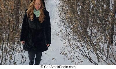 Fabulous woman walks through forest, background of winter landscape
