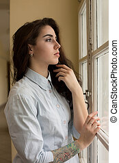 Fabulous young woman with curly hair and a tattoo on her arm posing near the window