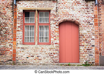 Facade brick old wall with painted door in a trendy color of the year 2019 Living Coral Pantone.