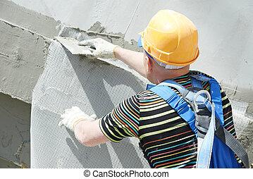 facade builder plasterer at work - builder worker plastering...
