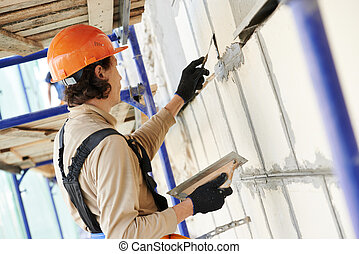 facade builder plasterer at work - builder worker works with...