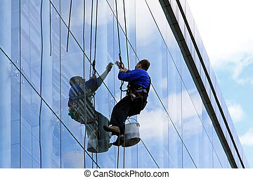 Facade cleaner at top of tall building