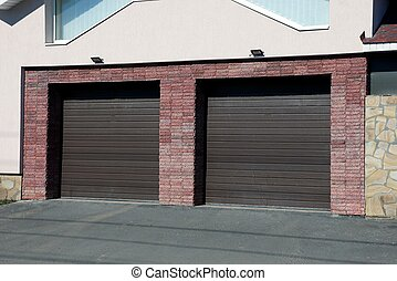 facade of a brown brick garage with two gates in the street