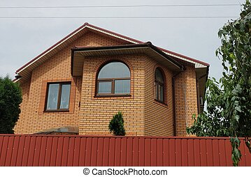 facade of a brown private house with windows on the street