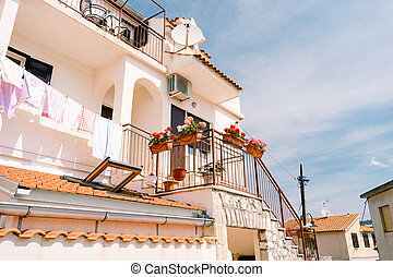 Facade of a building with a balcony and steps down and flower pots with flowers on a metal fence, against the background of the sky.