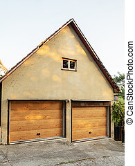 Facade of a garage with two gates wood trim
