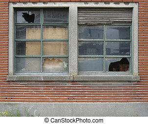 facade of abandoned building with broken windows and roller shutter