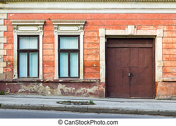 facade of an old building with two windows and door - two...
