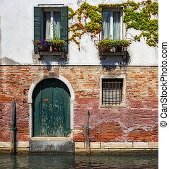 Facade of an old house on a canal in Venice