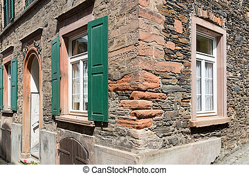 Facade of an old stone house with wooden shutters