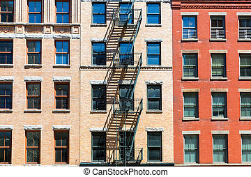 Facade of brick building with fire ladders.