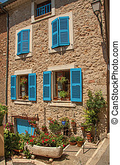 Facade of building with windows and blue shutters in Chateaudouble.