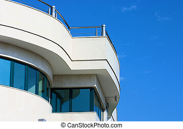 facade of modern building in blue and white tones on a background bright sky