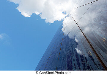 Facade of modern building with reflecting clouds