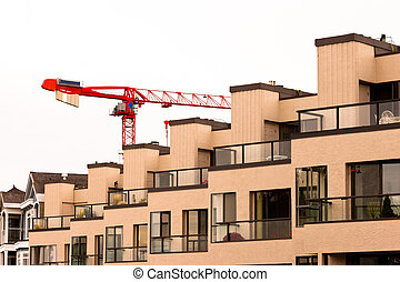 Tower crane over external facade of contemporary residential apartment block development with large glass windows and balconies for every unit.