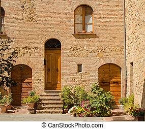 Facade of old brick house in Pienza