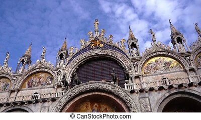 Amazing facade of Saint Mark Basilica decorated with ancient golden frescos and sharp spires against boundless bright blue sky