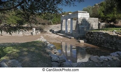 Facade of the ancient temple with columns reflection in the water, Kaunos, Dalyan valley, Turkey. 4k