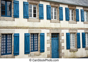Facade of traditional breton houses with blue shutters in...