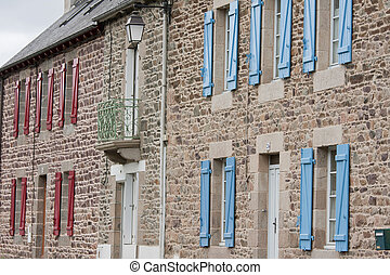 Facade of traditional breton houses with red and blue shutters