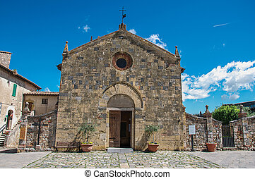 Facade view of an old church in a sunny day at the hamlet of Monteriggioni.