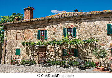 Facade view of an old house with creepers in the hamlet of Monteriggioni.