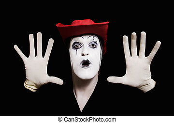 face and hands of mime with dark make-up in red hat