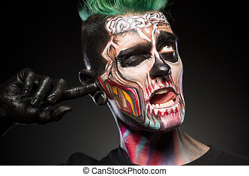 Face art concept, briht skull makeup on mans face.