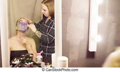 Face art. Model talking with make-up artist