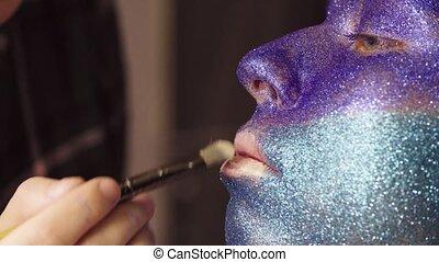 Face art. The make-up artist applying foundation