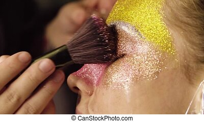 Face art. The make-up artist painting