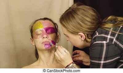 Face art. The make-up artist painting on the face of the...