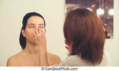 The make-up artist wiping the face of the model