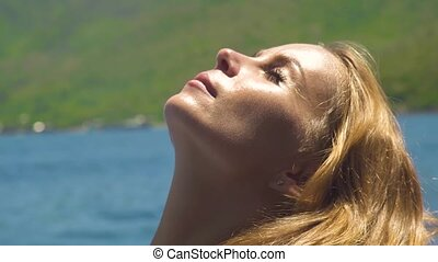 Face beautiful woman sunbathing at sunny day on sea landscape. Close up portrait young woman with golden and brown hair sunbathing on sun at sea beach.