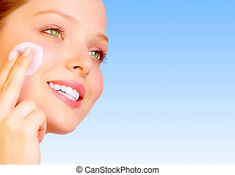 Face care - Pretty woman applying cream. Over blue...