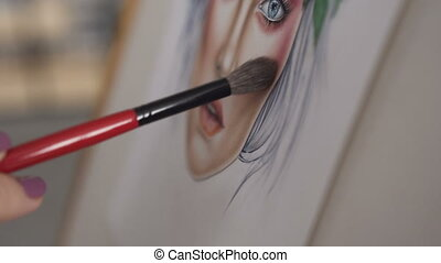 Face chart. Closeup: hand of woman makeup artist who draws a face chart using the brush for cosmeticks and palette of shadows