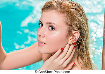 face close-up of a beautiful young girl in the pool