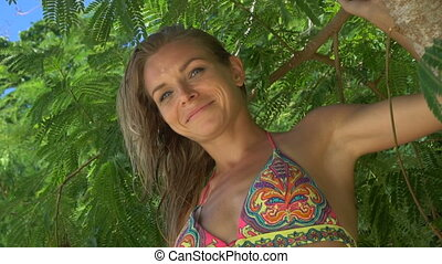 Face closeup of pretty blonde woman in bikini sitting on a branch