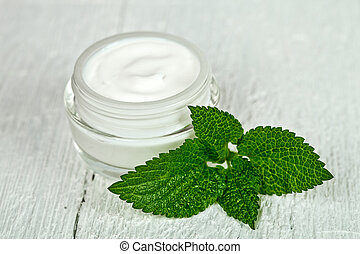 face cream in glass jar with green leaf of urtica on white wooden background