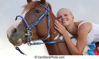 face happy girl rider sitting in the saddle on a horse...
