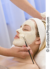Face Mask - A beautiful young brunette woman having a face...