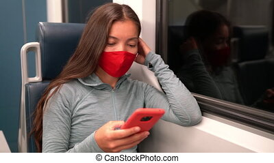 Face mask concept. Woman wearing mandatory mask in public transportation. Train transport commuter. Multiracial woman passenger using mobile smart phone with face covering on commute