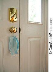 Face mask hanging from door handle on white door with sunlight coming in through window. C