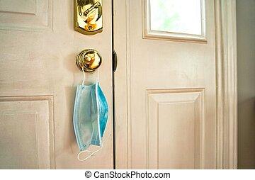 Face mask hanging from door handle on white door with sunlight coming in through window.
