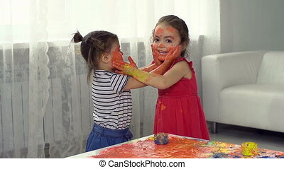 Face Mask - Two little girl friends smearing paint on their...