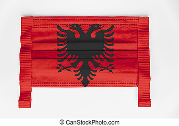 Face mask with Albania flag printed, on white background, isolated.