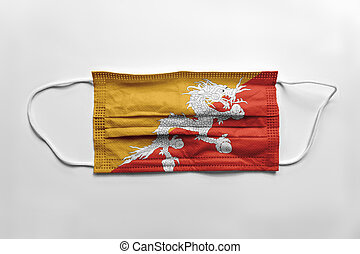 Face mask with Bhutan flag printed, on white background, isolated
