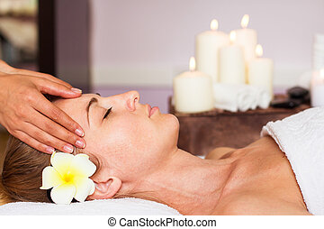 Face Massage. Close-up of a beautiful Woman Getting Spa Treatment.